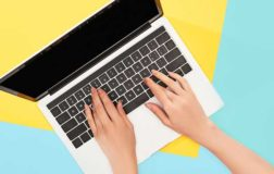 Hands on laptop keyboard with blue and yellow background