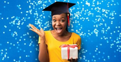 Woman with graduation cap holding present